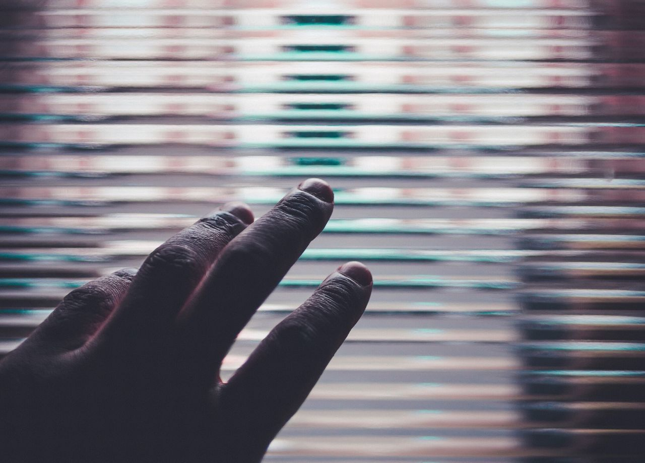 Cropped image of hand against window blinds