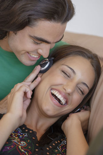 Young couple listening to music having fun 20-25 Years Old Headphones Laughing Adult Beautiful Woman Cheerful Couple - Relationship Emotion Females Front View Hairstyle Happiness Headshot Holding Indoors  Leisure Activity Lifestyles Portrait Positive Emotion Real People Smiling Togetherness Two People Women Young Adult