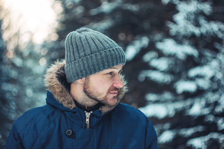 Portrait of man wearing hat against trees during winter