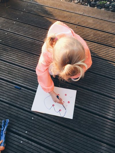High Angle View Of Girl Making Drawing In Book On Table