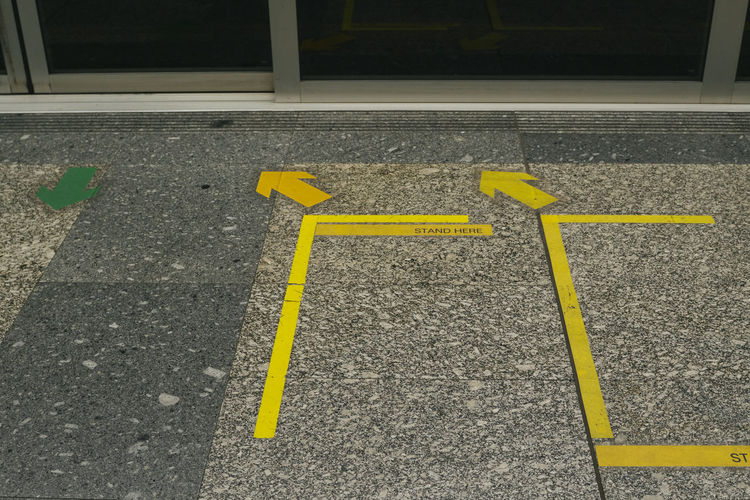 High angle view of yellow arrow sign on road