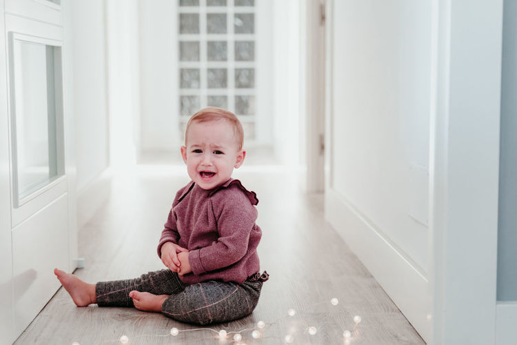 Portrait of cute girl sitting on floor at home