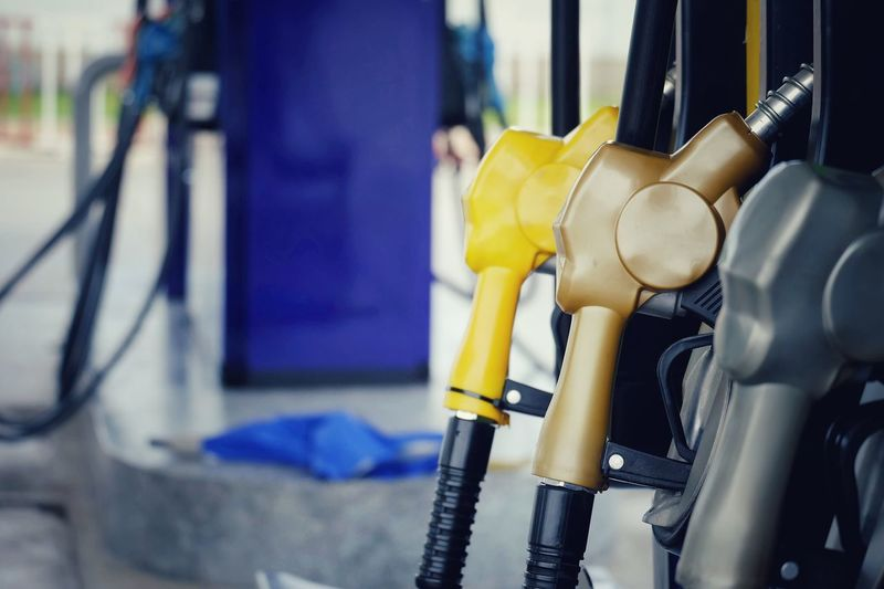 Close up nozzle fuel at pump gas station Transportation Industry Equipment Fuel And Power Generation Environment Technology Power Energy Oil Gasoline Petrol Petroleum Car Vehicle Automobile Marketing Cost Growth Payment Pollution