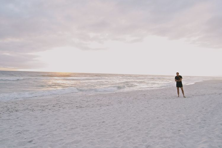 Man Standing On Shore At Beach Against Sky
