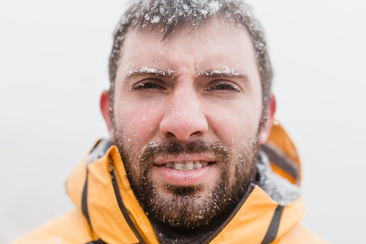 Close-Up Portrait Of Smiling Man In Snow