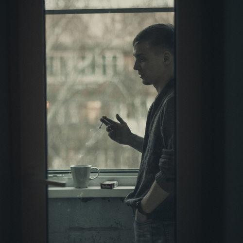 Side view of man smoking at window