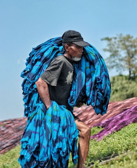 Man carrying blue textile while walking on field against clear sky