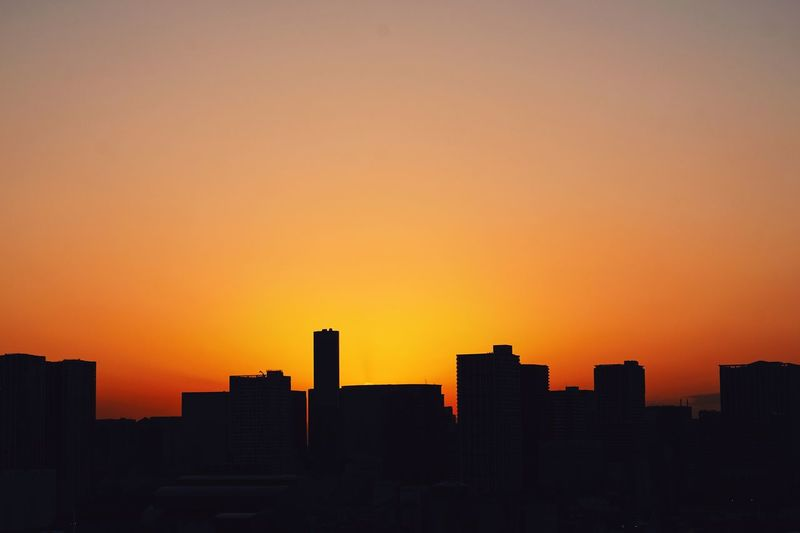 Silhouetted cityscape against orange sky