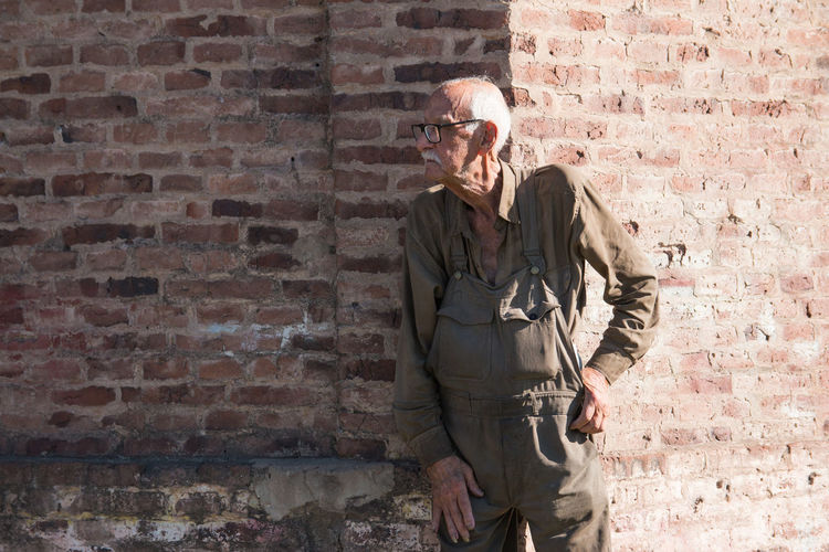 Portrait of old man against bricked wall