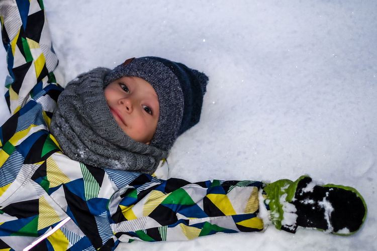 High angle portrait of boy lying on snow covered field