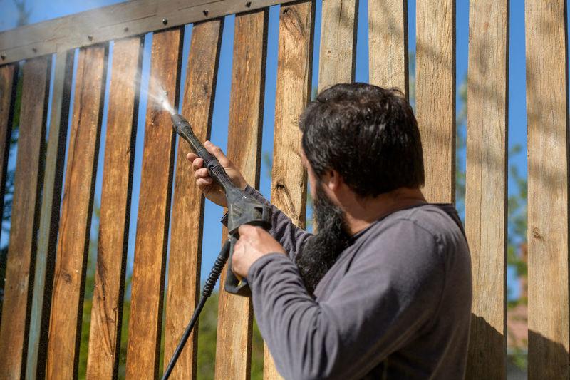 Man playing with water gun in back yard