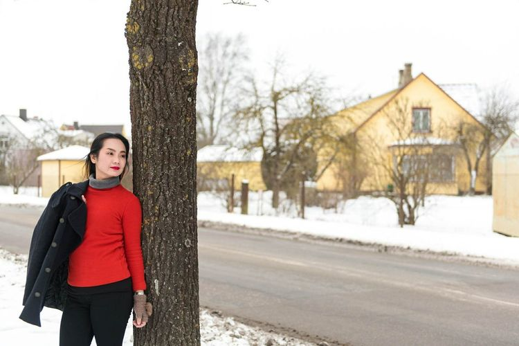Woman standing by tree in city during winter