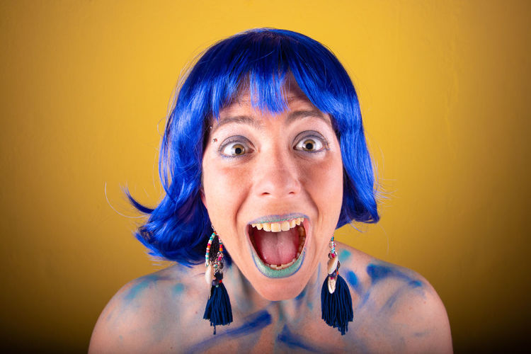 Close-up portrait of young female model with blue wig shouting against yellow background