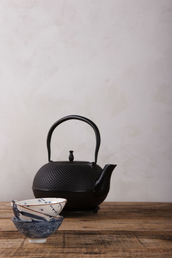 Close-up of tea cup on table against wall