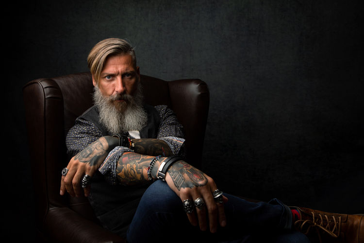 Portrait Of Hipster Man Sitting On Armchair Against Gray Wall