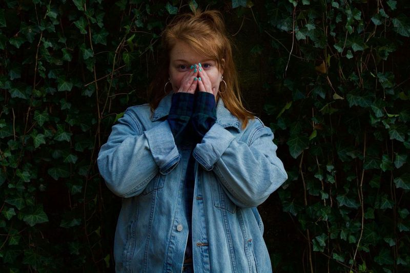 Portrait of young woman covering mouth while standing against plants