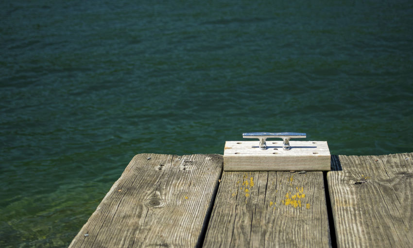 Cleat on wooden dock against lake