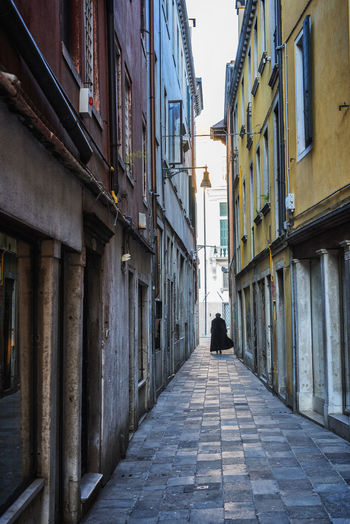 Rear view of man walking on narrow alley amidst buildings