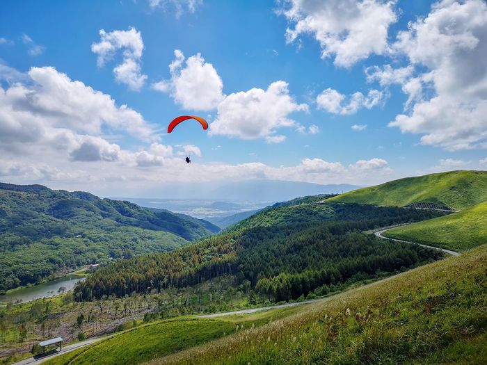 Scenic view of man paragliding over field against sky