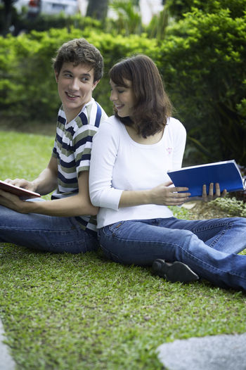 Couple reading books while sitting on field