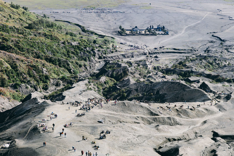 High angle view of people walking on mountain during sunny day