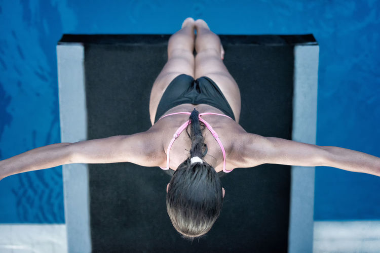 Female Diver Preparing On The Platform, Shot From Above Swimming Diving Athlete Back Dive Diving Diving Board Individual Sports Standing Water Sport Woman Blue Directly Above Dive Female Muscular Build One Person Outdoors Pool Preparation  Sport Strength Swimming Pool Water Young Adult Young Women