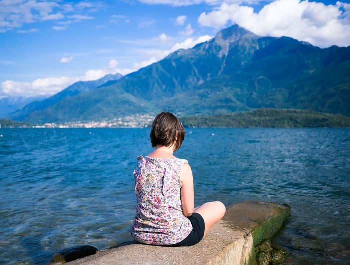 Rear View Of Woman Sitting On Retaining Wall By Lake