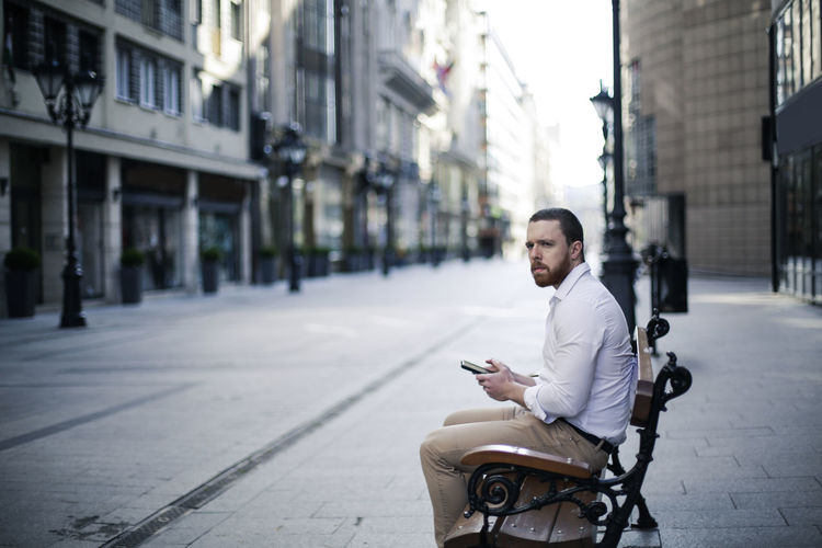 Side view of businessman using smart phone while sitting on bench in city