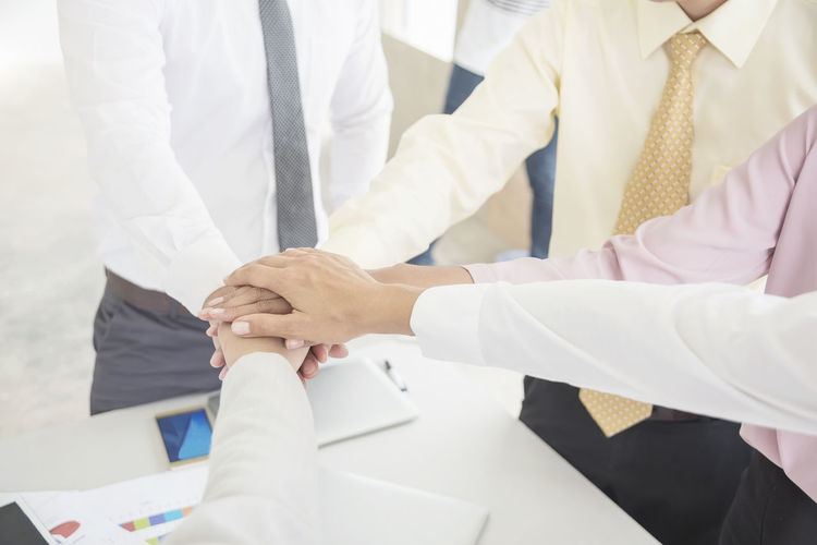 Cropped image of colleagues stacking hands in office