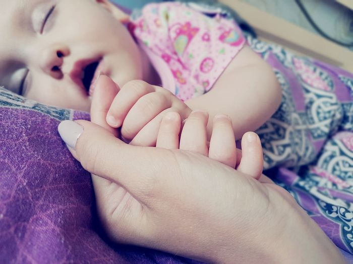 Close-Up Hand Touching Baby Lying On Bed