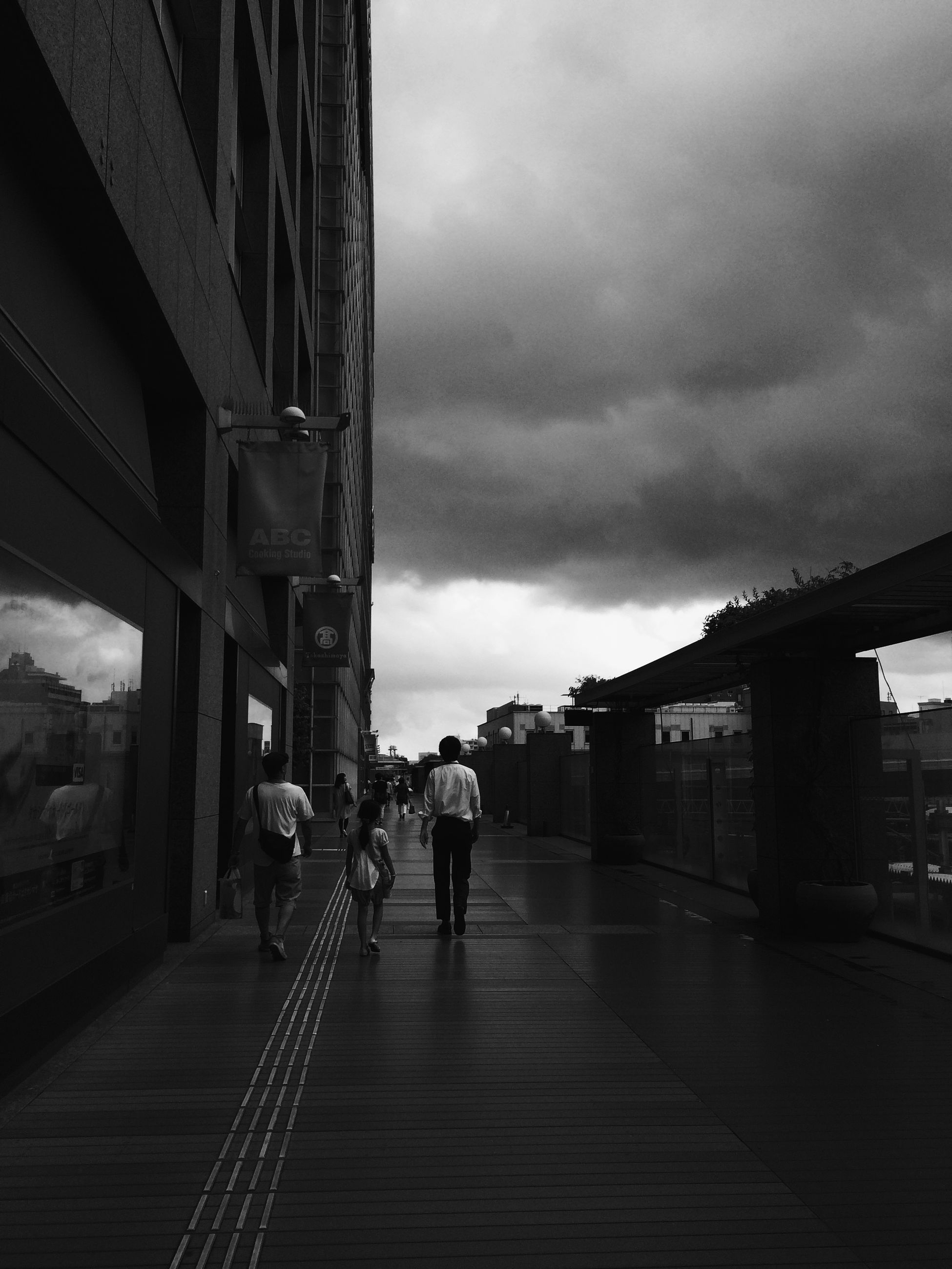 architecture, built structure, building exterior, sky, walking, men, cloud - sky, city, the way forward, person, lifestyles, full length, city life, cloudy, rear view, cloud, transportation, street, railing