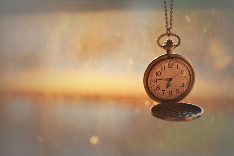 Close-up of clock hanging against blurred background