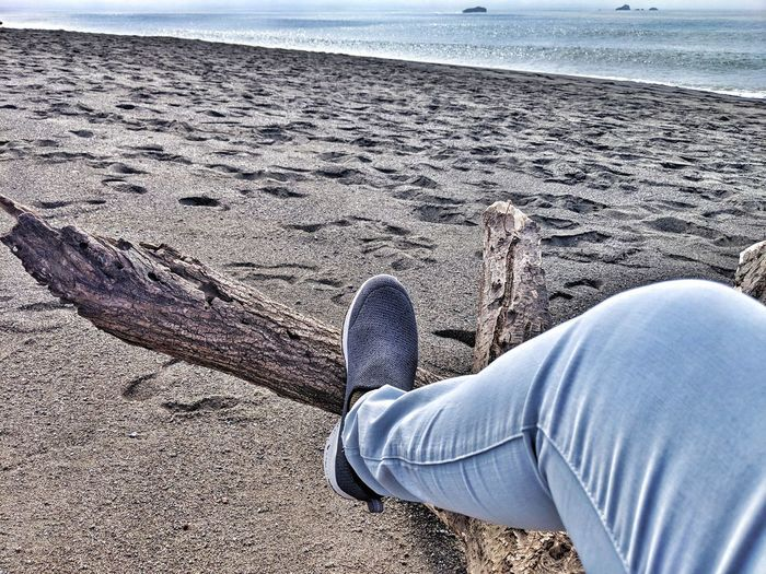 My quiet place. Jeans Light Blue Black Shoe Resting Driftwood Elevated Creased Ocean Sabdy Seam Foot Background Therapeutic Low Section Water Beach Sand Sea Men Human Leg Shoe High Angle View Close-up Shore Footwear Ocean Sandy Beach Calm Wave Seaside