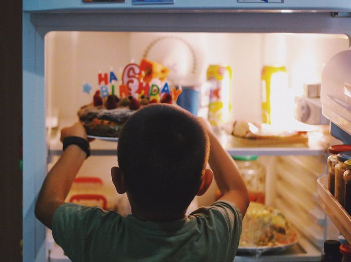 Rear view of boy putting cake in refrigerator