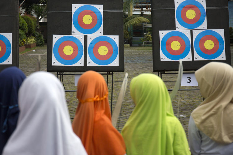 Girl Wearing Hijab Plays Archery Archery Target Rear View Group Of People People Lifestyles Multi Colored Standing Side By Side Clothing Hijab Jilbab Sport Competition Teenager Girl