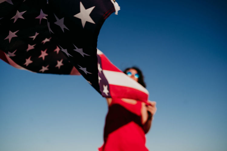 Low angle view of woman with american flag against clear blue sky