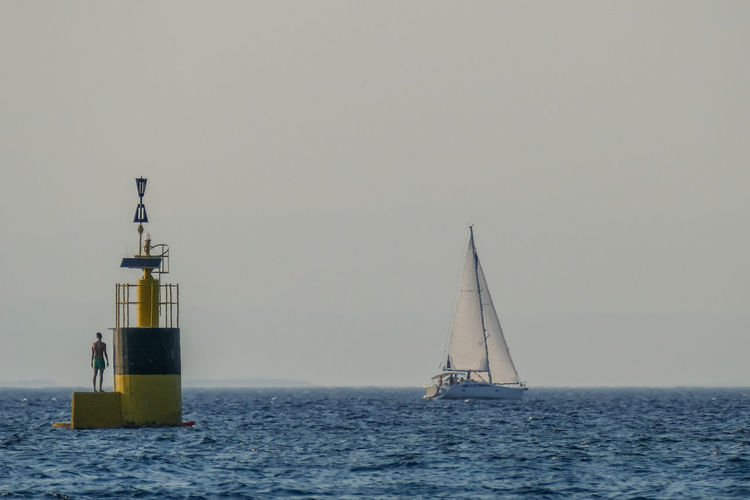 Sea Water Nautical Vessel Transportation Waterfront Sailboat Mode Of Transportation Sailing Horizon Over Water Sky Horizon No People Nature Clear Sky Lighthouse Copy Space Tower Guidance Day Outdoors Yacht