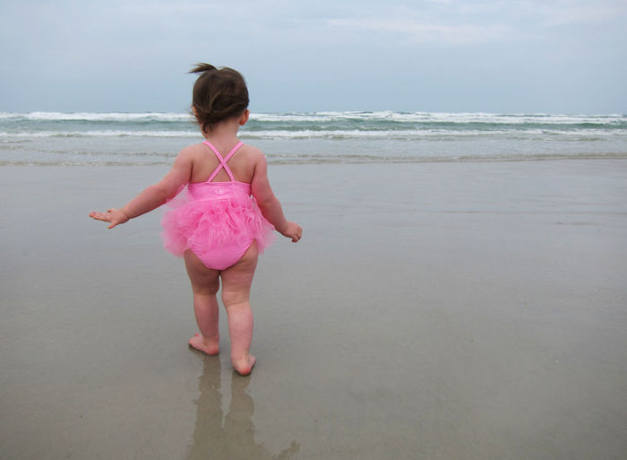 Rear view of baby girl walking on sea shore