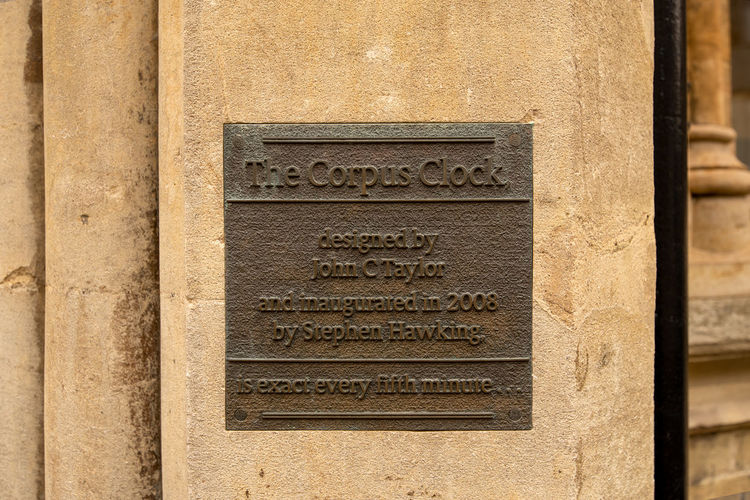 A bronze plaque embedded in a lime stone wall for the Corpus Clock in Cambridge, UK. Architecture Art And Craft Built Structure Clock Close-up Communication Corpus Clock Craft Engraved Image History No People Plaque Script Text The Past Tombstone Travel Destinations Western Script