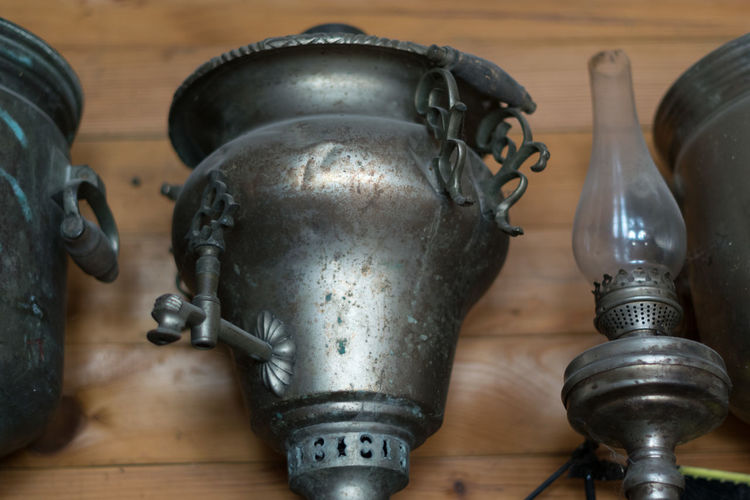 Low angle view of oil lamp by antique containers