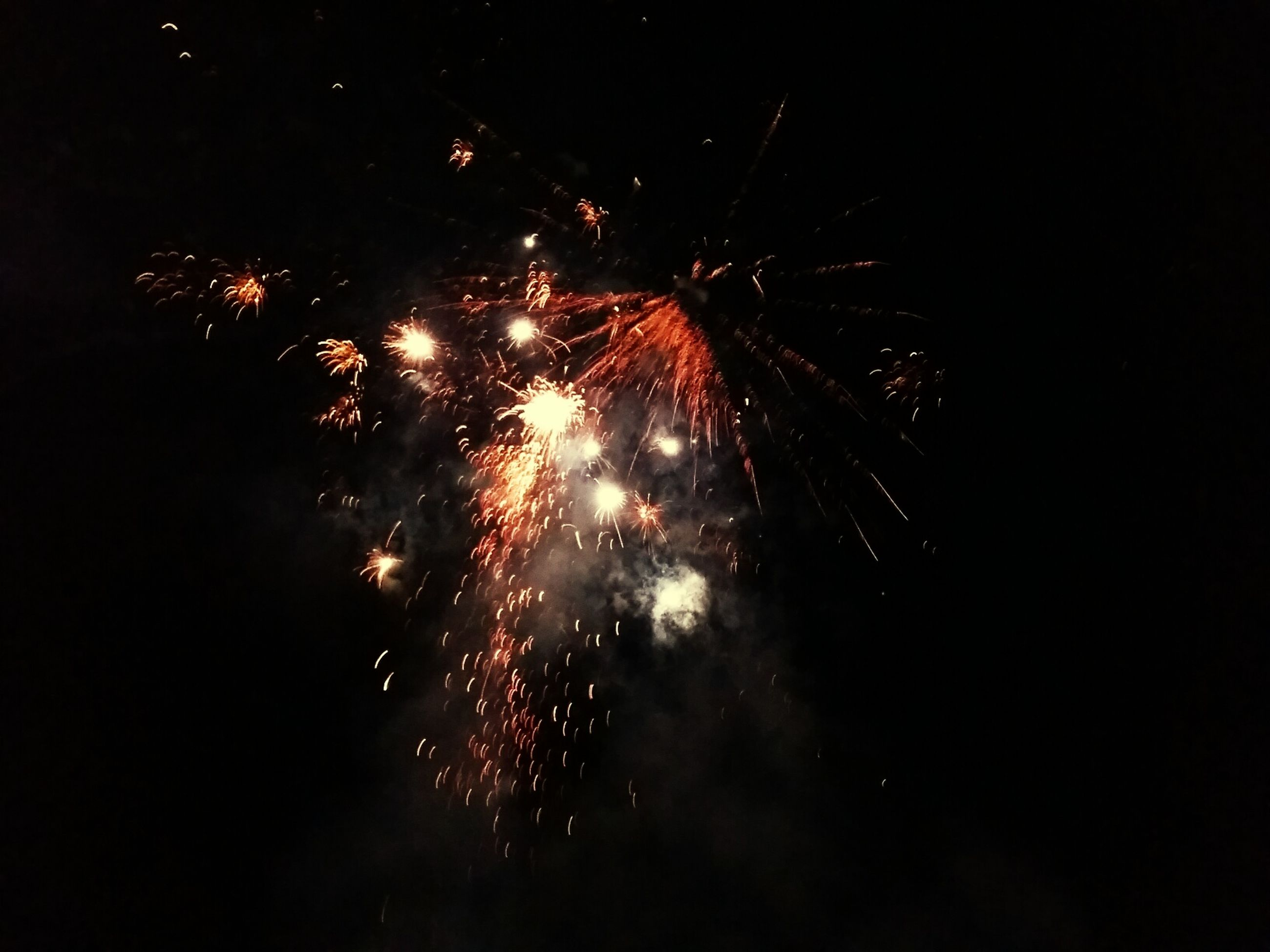 night, firework display, illuminated, long exposure, exploding, firework - man made object, motion, celebration, arts culture and entertainment, glowing, sparks, blurred motion, low angle view, event, firework, sky, entertainment, outdoors, celebration event, no people