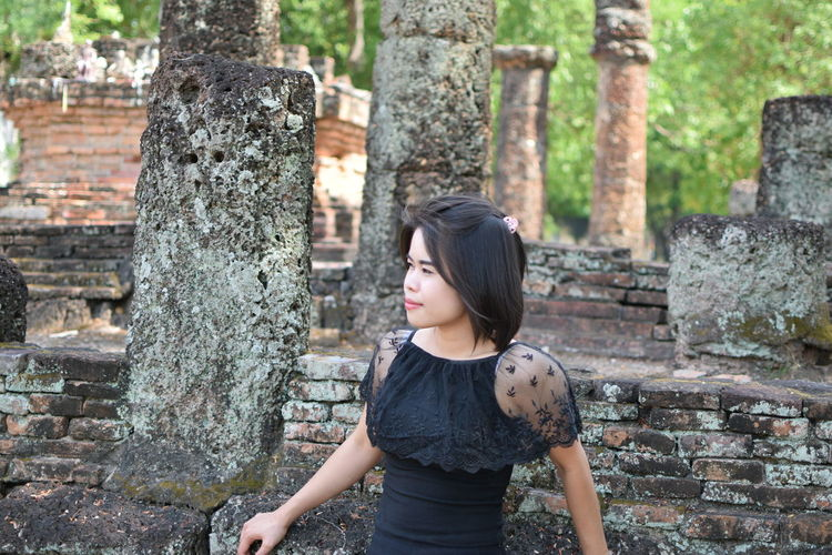 Young woman looking away while standing against old ruin