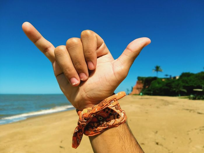 Close-up of man showing shaka sign at beach against blue sky