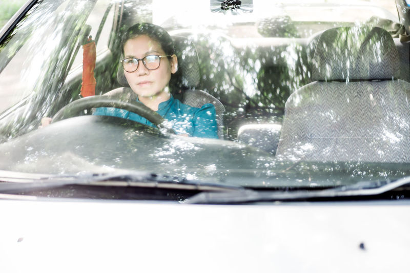 Portrait of happy young woman in car