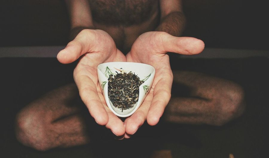 Midsection of shirtless man holding herbs in bowl