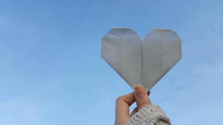 Low angle view of hand holding heart shape against blue sky