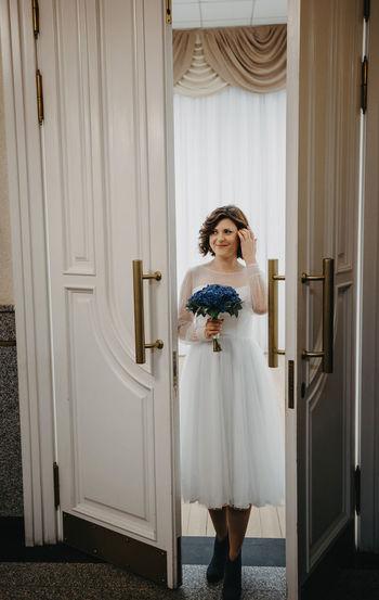 Portrait of young woman standing against door