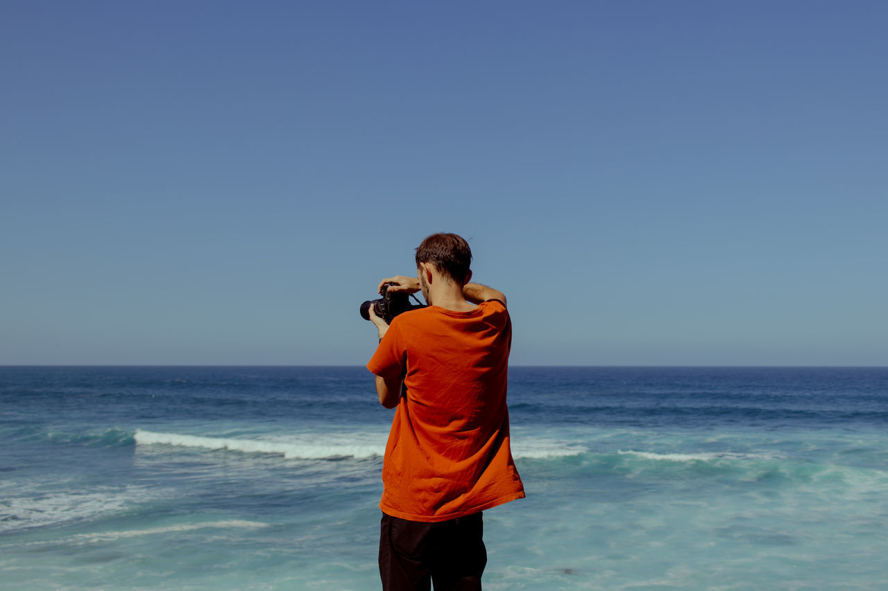 REAR VIEW OF PHOTOGRAPHER PHOTOGRAPHING SEA AGAINST SKY
