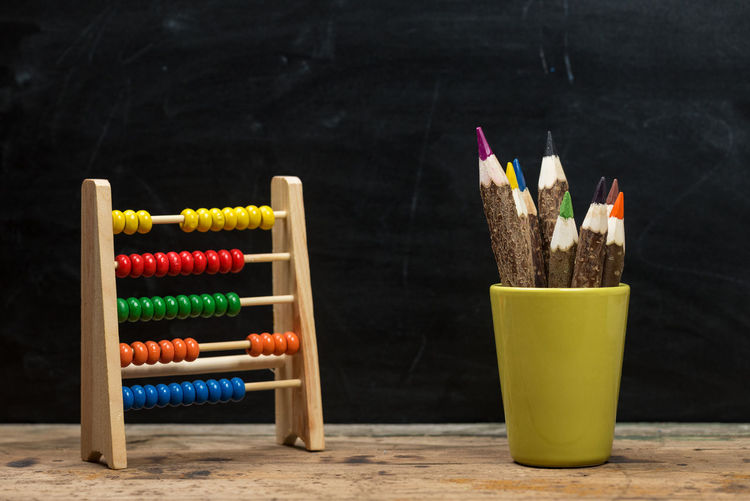 Close-up of colored pencils in desk organizer by abacus on table against black background