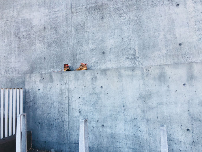 Low angle view of shoes on concrete wall